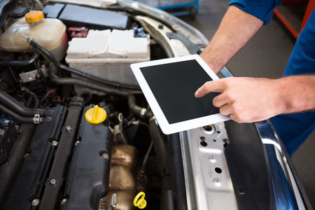 maintenance: Mechanic using tablet to fix car at the repair garage