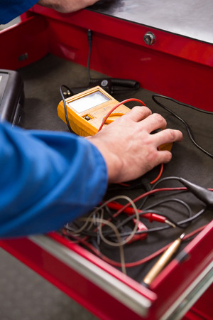 diagnostic tool: Mechanic taking a diagnostic tool from drawers at the repair garage Stock Photo