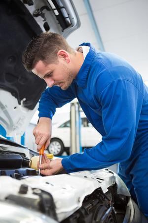 engine bonnet: Mechanic using screwdriver on engine at the repair garage