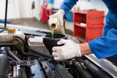 mechanic: Verter Mecánico aceite en coche en el garaje de reparación Foto de archivo