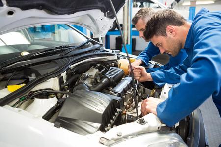 ingeniero: Equipo de mec�nicos que trabajan juntos en el garaje de reparaci�n Foto de archivo