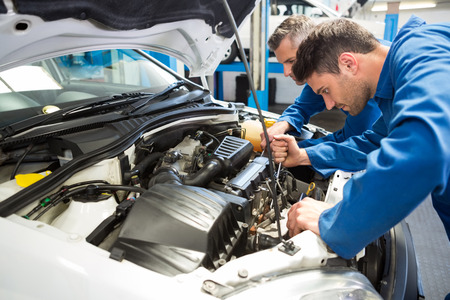 Quipe de mécaniciens de travailler ensemble dans le garage de réparation Banque d'images - 36355458