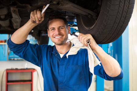 mecanico: Mec�nico examinar bajo el coche en el garaje de reparaci�n Foto de archivo