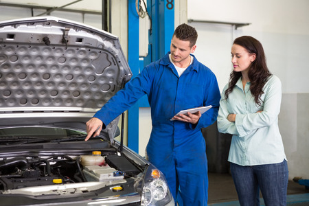 Mechanic showing customer the problem with car at the repair garage Stock Photo