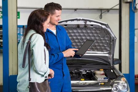 정비사가 고객에게 수리 차고에서 차량 문제를 보여줍니다.