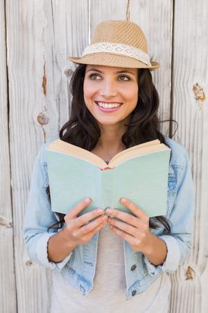persona leyendo: Bastante inconformista leyendo un libro contra la cerca de madera blanqueada Foto de archivo