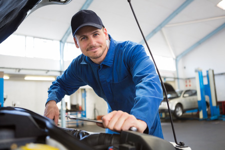 mechanic: Mecánico examinar bajo el capó del coche en el garaje de reparación Foto de archivo