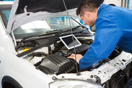 motor coche: Mecánico que usa la tableta para fijar coche en el garaje de reparación