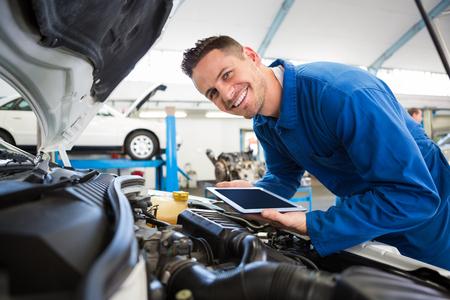 Monteur met behulp van tablet op auto bij de reparatie garage