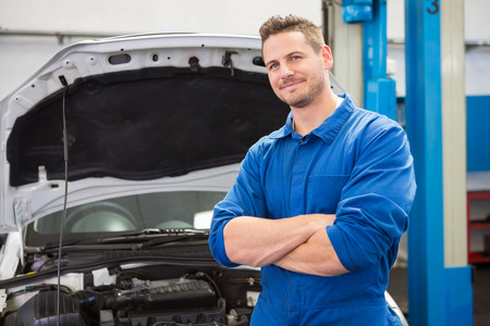 young adult men: Mechanic smiling at the camera at the repair garage Stock Photo