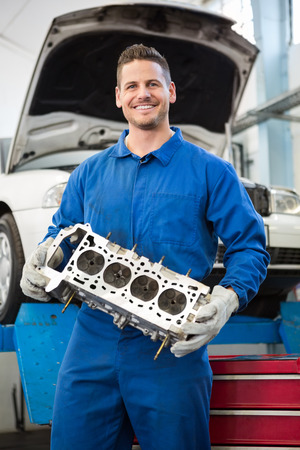 Smiling mechanic holding an engine at the repair garage photo