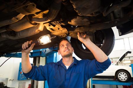 under: Mechanic shining torch under car at the repair garage Stock Photo