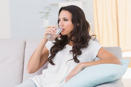 vaso de agua: Pretty morena de agua potable en el sofá en casa, en la sala de estar Foto de archivo