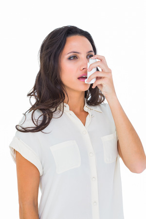 asthmatic: Asthmatic brunette using her inhaler  on white background Stock Photo