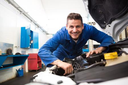 Mechanic working under the hood at the repair garage Stok Fotoğraf
