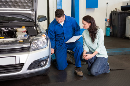 mechanic car: Mechanic showing customer the problem with car at the repair garage Stock Photo