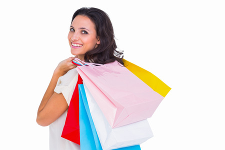 Pretty brunette with shopping bags on white background photo