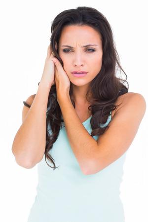 dolor de oido: Pretty morena conseguir un dolor de o�do en el fondo blanco
