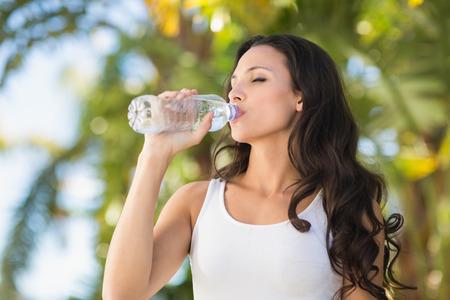 晴れた日に水の飲料ボトルにかなりブルネット