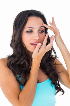 putting in: Pretty brunette putting in contact lens on white background