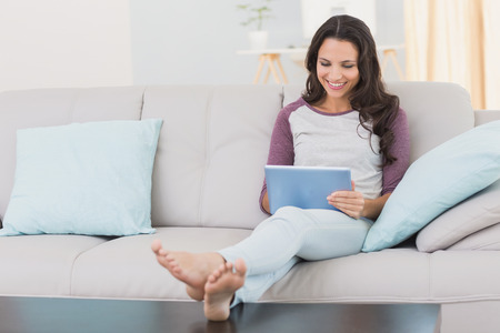 long hair woman: Pretty brunette using her tablet at home in the living room