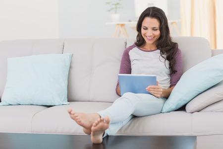 mujeres sentadas: Pretty morena con su tableta en casa en la sala de estar