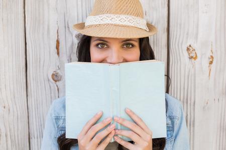 mujer leyendo libro: Bastante inconformista leyendo un libro contra la cerca de madera blanqueada Foto de archivo