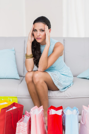 regretful: Regretful brunette with many shopping bags at home in the living room Stock Photo