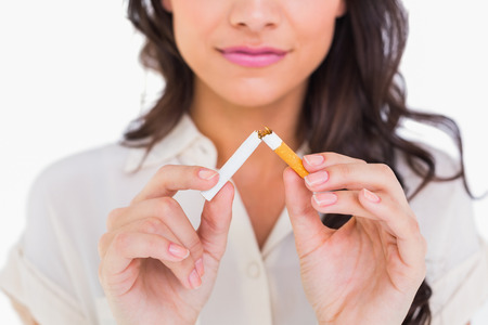 cancerous: Brunette snapping her cigarette on white background