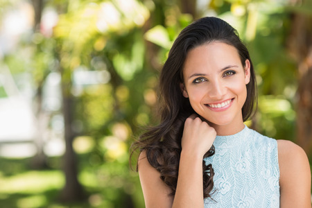 woman long hair: Stylish brunette smiling at camera on a sunny day Stock Photo