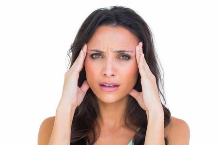 wincing: Pretty brunette getting a headache on white background Stock Photo