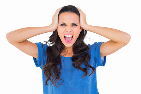 outraged: Angry brunette shouting at camera on white background