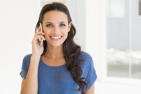 Pretty brunette talking on phone at home beside window Stock Photo
