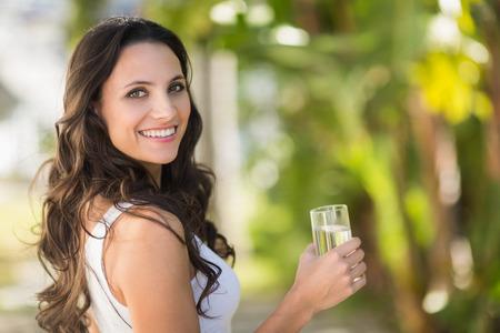 belle brunette: Jolie brune verre � boire de l'eau sur une journ�e ensoleill�e