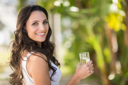 attractive female: Pretty brunette drinking glass of water on a sunny day