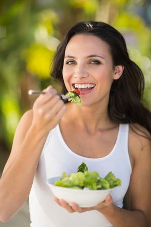 dia soleado: Pretty morena comer tazón de ensalada en un día soleado