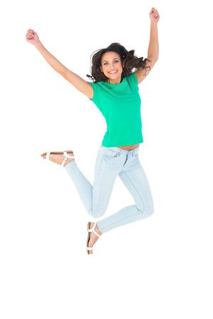 salto largo: Pretty morena saltando y sonriendo sobre fondo blanco