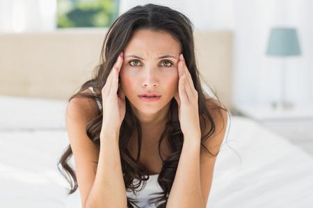 nerveux: brunette Worried assis sur le lit � la maison dans la chambre Banque d'images