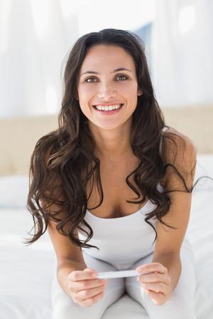 pregnancy test: Excited brunette waiting on pregnancy test at home in bedroom