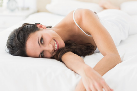 Happy brunette lying on bed at home in bedroom Stock Photo