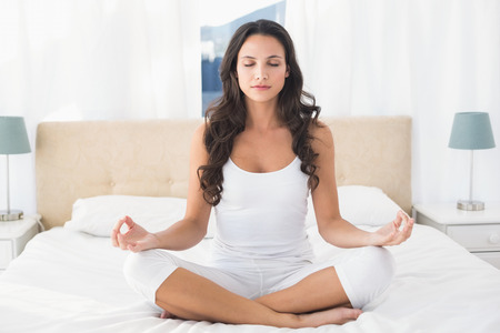 lotus pose: Calm brunette doing yoga on bed at home in bedroom