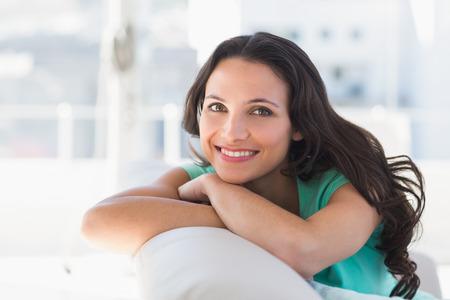 Mooie brunette ontspannen op de bank thuis in de woonkamer