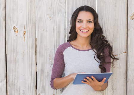 person woman: Pretty brunette using a tablet pc against bleached wooden fence Stock Photo