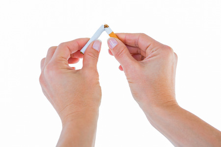 fag: Close up of a woman breaking cigarette on white background