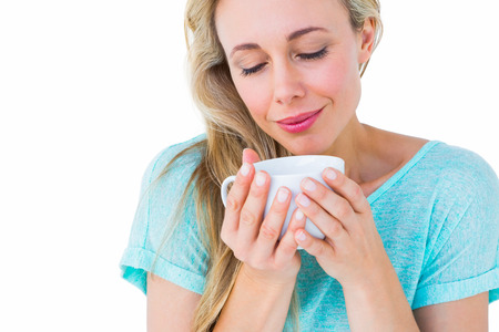 hot beverage: Smiling blonde with hot beverage relaxing on white background Stock Photo