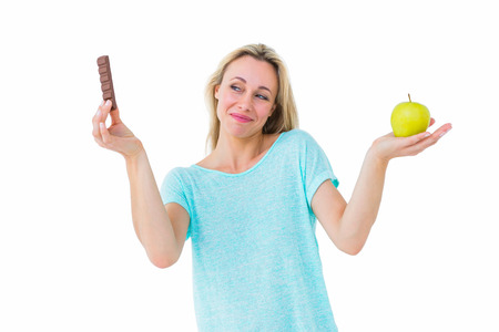 health fair: Smiling blonde holding bar of chocolate and apple on white background