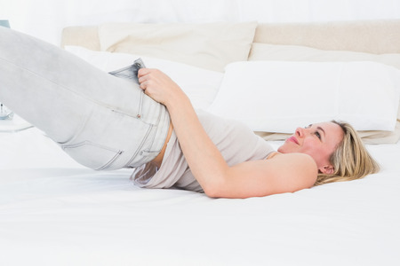 forcing bed: Focused blonde forcing to close her jeans on the bed in hotel room Stock Photo