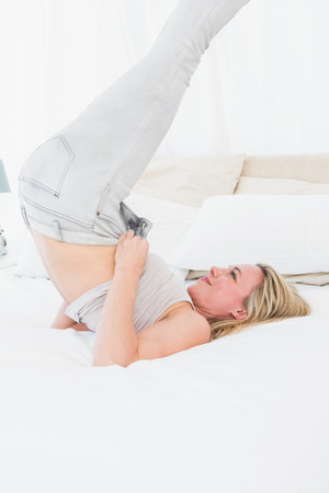 forcing bed: Blonde struggling to close her jeans on the bed in hotel room