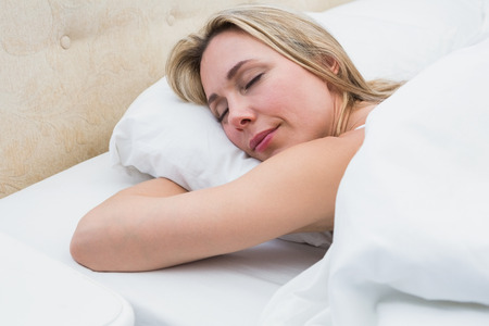 Pretty blonde lying in bed sleeping at home in the bedroom photo