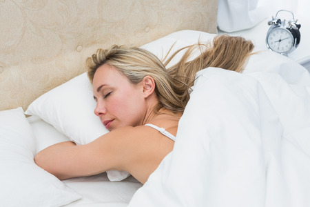Pretty blonde sleeping in bed with alarm clock on bedside table in the room photo